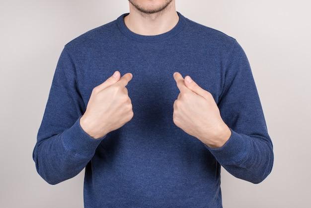 근접 촬영 자른 캐주얼 풀오버 고립 된 회색 벽을 입고 자기 자신을 가리키는 만족 자신감 남자의 사진 초상화를 자른