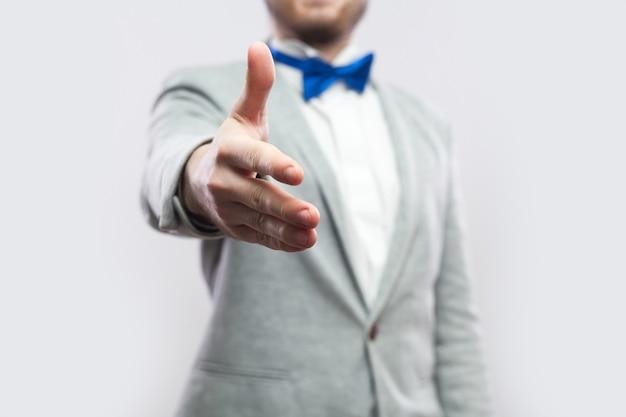 Обрезанный крупным планом портрет красивого бородатого мужчины в повседневном сером костюме и синем галстуке-бабочке, стоя и давая рукопожатие приветствию, помощи или поздравлениям. закрытый студийный снимок, изолированные на светло-сером фоне