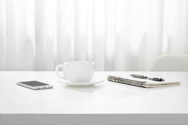 Closeup of a cup of coffee, a notebook and pen, and a smartphone on a white desk, indoors