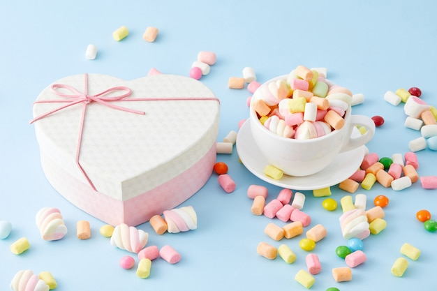Closeup of a cup filled with marshmallows and a heart-shaped box isolated
