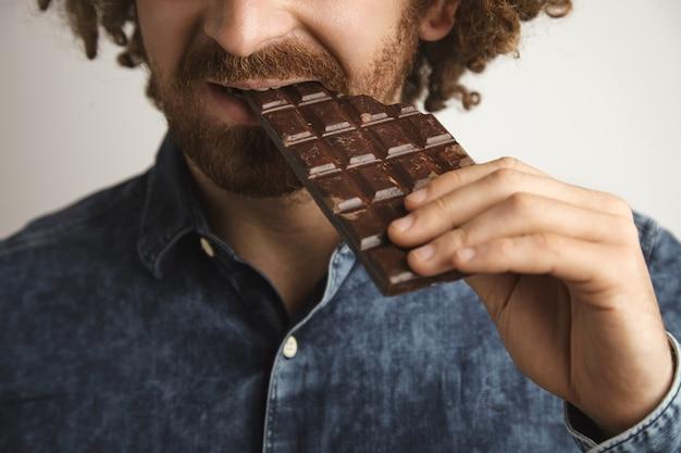 Primo piano capelli ricci felice uomo barbuto con pelle sana morde organico appena sfornato barretta di cioccolato con il lato della bocca, messa a fuoco ravvicinata sulla bocca