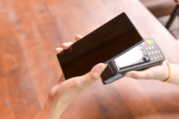Closeup of a customer using her smartphone and nfs technology to payment
