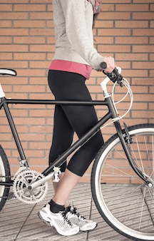 Closeup of customized fixie bike and beautiful young sportive woman over a orange brick wall on the background