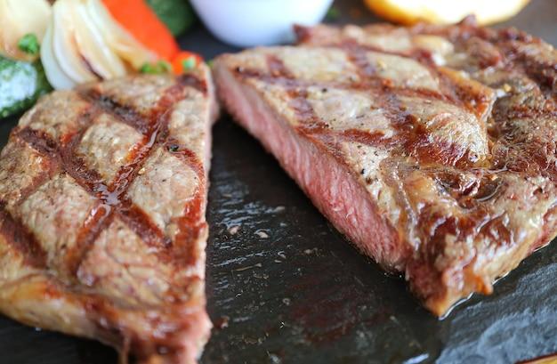 Closeup cut juicy medium grilled ribeye steak served on hot stone plate