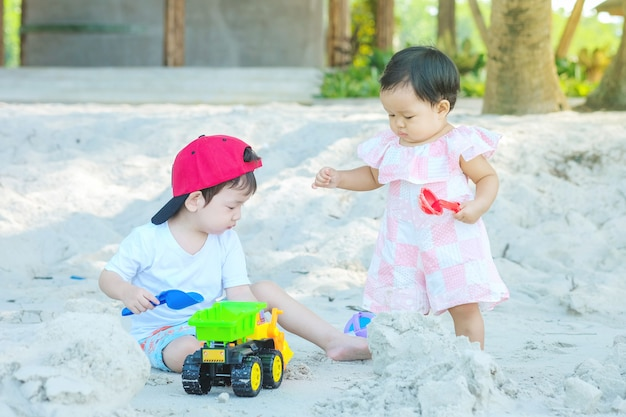 Closeup cute asian boy and girl play with sand and toy on beach textured background
