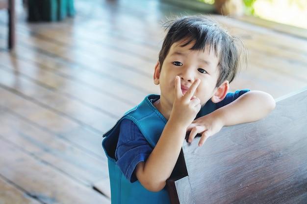 クローズアップかわいいアジアの子供はボートを待っているライフジャケットとの戦いの手段で2本の指を保持します。
