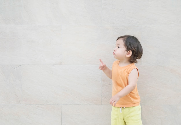 Closeup cute asian kid point to copy space of picture on marble stone wall textured background