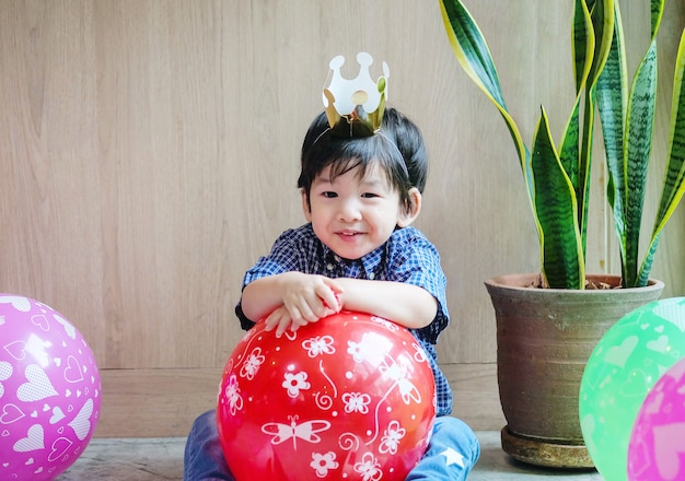 Closeup cute asian kid with paper crown and balloon in birthday party in room textured background with copy space