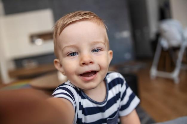 Closeup of cute blond toddler taking selfie. Premium Photo