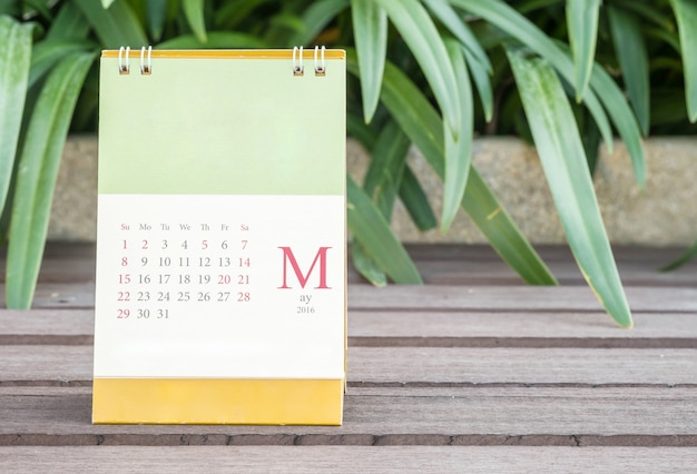 Closeup cute calendar in may on blurred garden view background