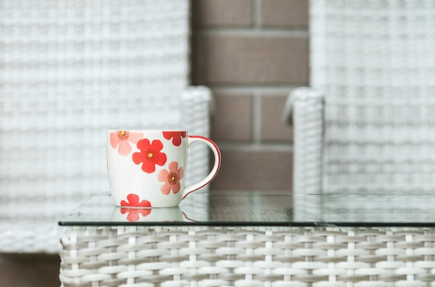 Closeup cute cup on blurred wood weave table and chair textured background