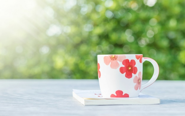 Closeup cute cup of coffee white book on blurred concrete desk and garden view in the morning textured background