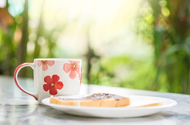 Closeup cute cup on marble desk and garden view in the morning