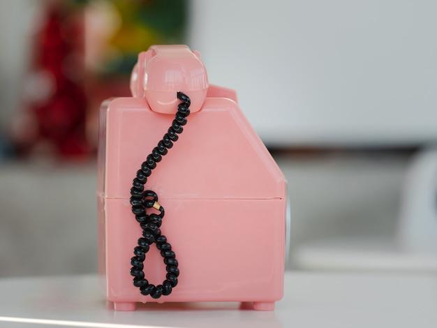 흰색 테이블에 장식된 귀여운 분홍색 파스텔 구식 전화기