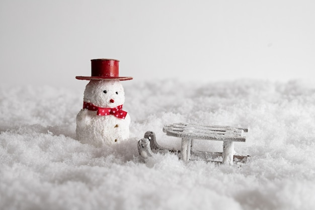Closeup of a cute snowman toy and a sleigh in the snow,