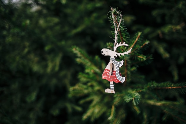 Closeup of a cute wooden deer-shaped christmas ornament hanging from a pine tree
