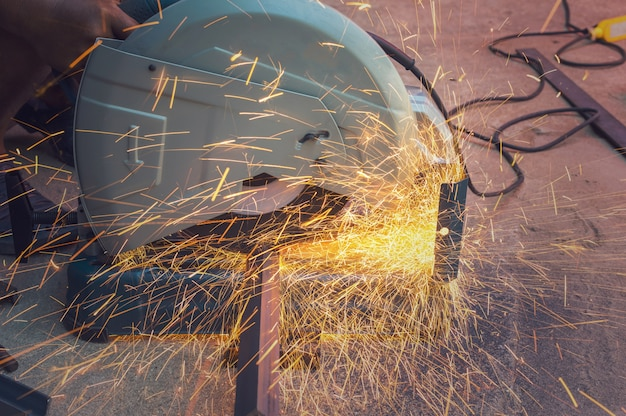 Closeup cutting process of metal material with sparks, industrial concept