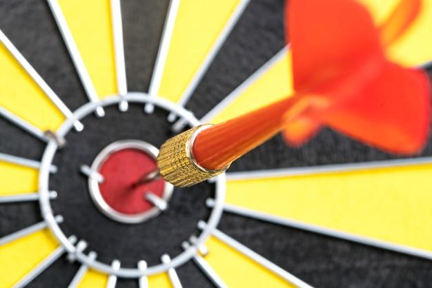 Closeup dart target with arrow on bullseye, goal target success business investment