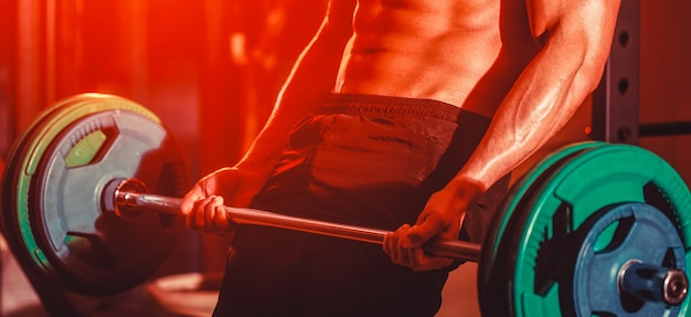 Closeup deadlift barbells workout. workout the gym. athletic man with six pack, perfect abs.