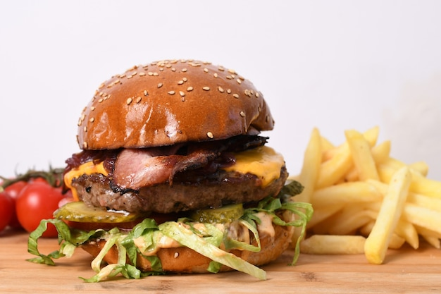 Closeup of a delicious beef burger on a wooden board with french fries and tomatoes on it