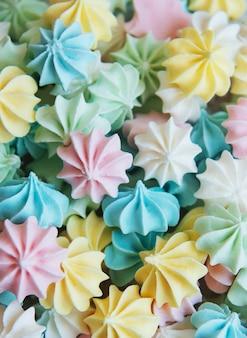 Крупным планом вкусное печенье безе пастельных тонов поверхность французской выпечки сладкие хрустящие завитки конфеты
