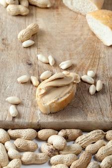 テーブルの上のおいしいピーナッツバターと白パンのクローズアップ、パンとピーナッツの簡単な朝食を準備するための材料、ピーナッツペーストのローストピーナッツ