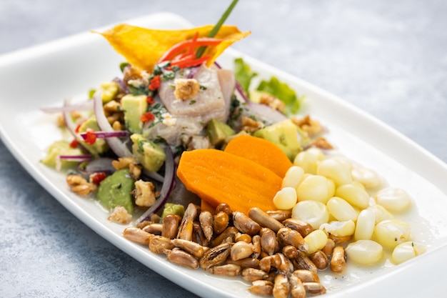 Primo piano di una deliziosa insalata con verdure ed erbe in un piatto sul tavolo