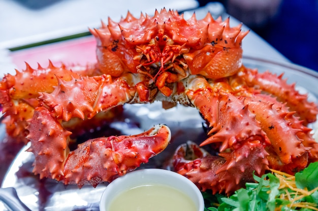 Closeup of delicious tasty boiled freshly prepared red king crab on metal dish with lemon, greens, sauce.