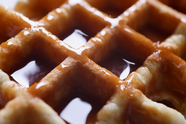 Closeup of delicious viennese waffles with caramel syrup