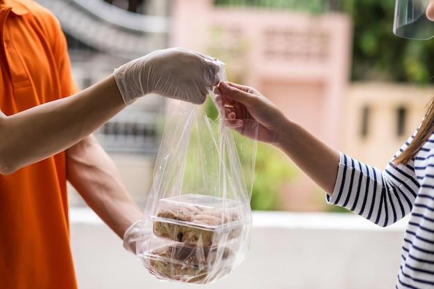 장갑과 근접 촬영 배달원 집에서 얼굴 방패와 함께 고객에게 빵 빵집을 제공합니다. 코로나 바이러스 전염병이 진행되는 동안 온라인으로 안전하게 음식을 주문하십시오.