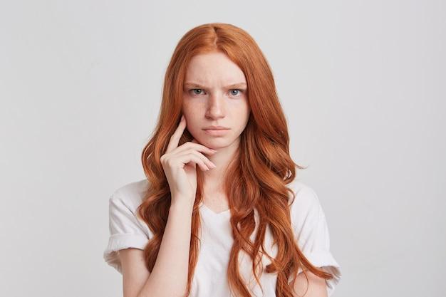 Primo piano della giovane donna depressa della testarossa sconvolta con capelli ondulati lunghi