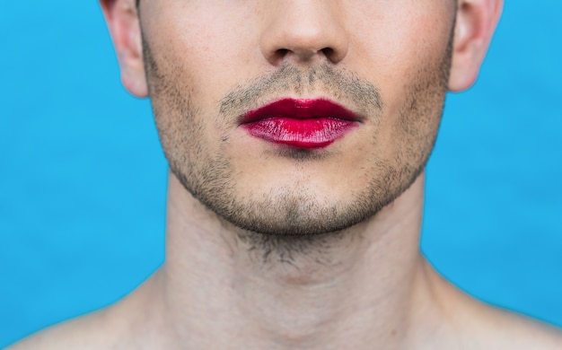 파란색 벽에 립스틱을 가진 남자의 근접 촬영 세부 사항