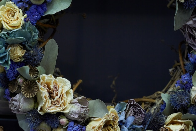 Closeup detail of a vintage wreath of dried flowers in pastel colors, selective focus