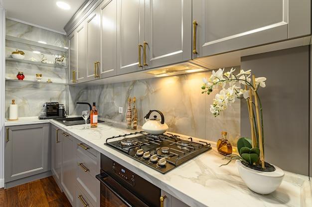 Крупным планом детали серо-белой современной классической кухни, выполненной в современном стиле