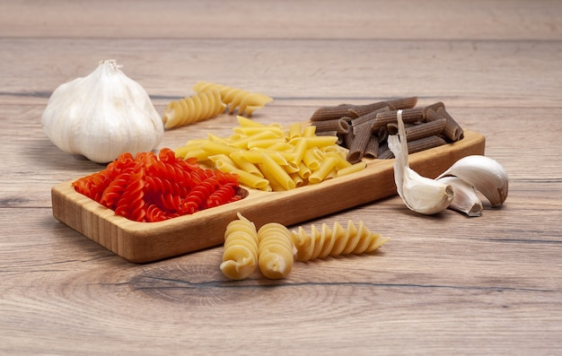 Closeup of different raw kinds of pasta with garlic cloves on a wooden table