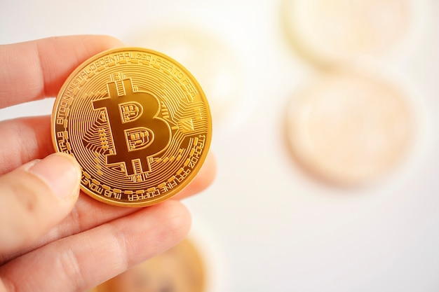 Closeup digital currency coin in womans hand on blurred background
