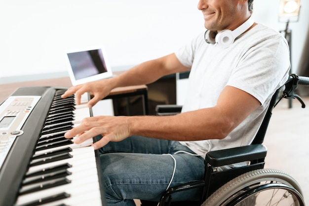 Closeup of disabled male hands plays synthesizer.