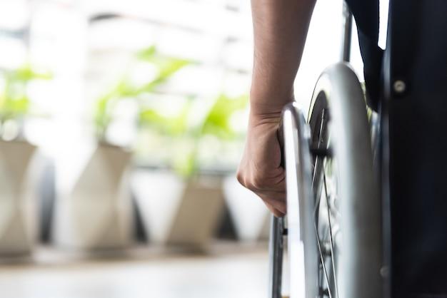 Closeup disabled man hand on wheel of wheelchair.