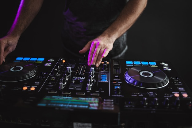 Closeup of a dj working under the colorful lights in a studio