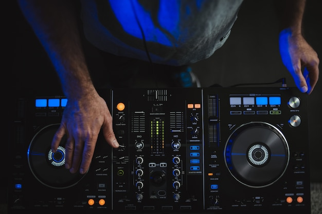 Closeup of a dj working under the colourful lights in a studio