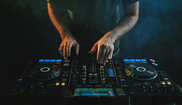 Closeup of a dj working under the lights