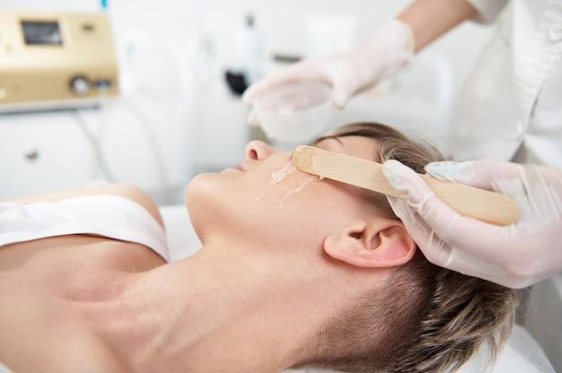 Крупный план. врач косметолог наносит гель с обезболивающим на лицо женщины для подготовки к процедуре лазерной эпиляции в оборудованной спа-клинике.