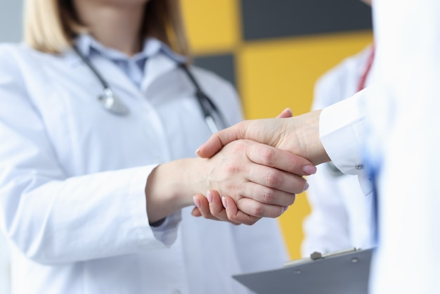 Closeup of doctor and patient handshake in clinic. council of doctors concept