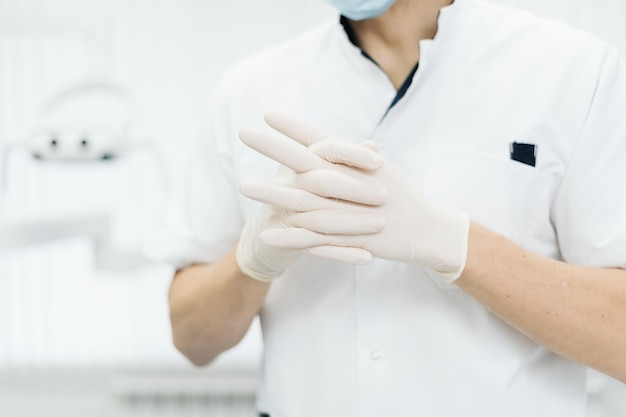 Mani del dottore del primo piano in guanti