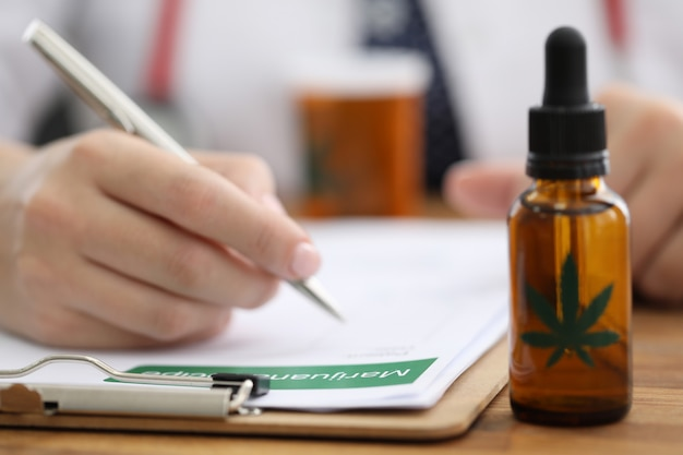 Closeup doctors hand writing prescription for hemp