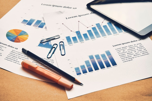 Closeup documents of financial statistics dummy with graph, chart, tablet. business analysis concept