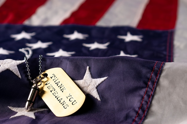 Closeup of a dog tag with the text thank you veterans on a flag of the united states background.