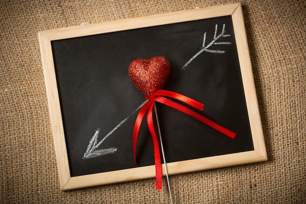 Closeup of drawn on chalkboard arrow going through decorative heart