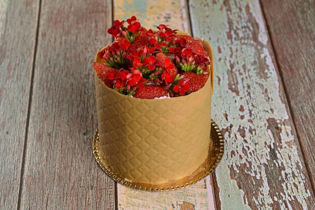Closeup of a dress cake, wrapped in a textured layer of salted chocolate caramel, with strawberries and red kalanchoe flowers.