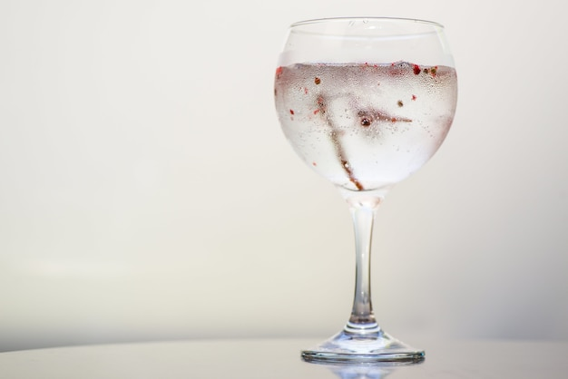 Closeup of a drink in a glass under the lights against a white background